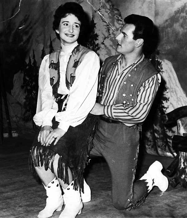 glenn on stage on one knee with his leading lady on his other knee both wearing country and western clothing in black and white