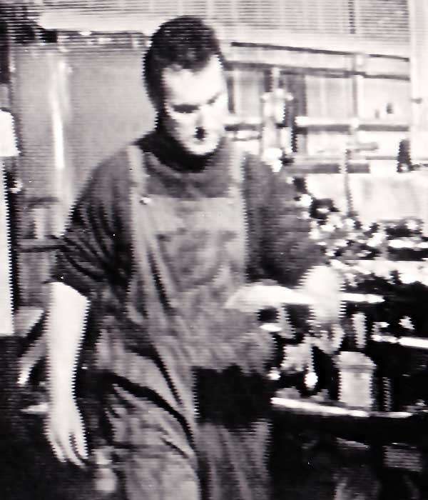 close up of sheffield actor sean glenn in machine engineering clothing including pocketed dungarees working in a machine shop
