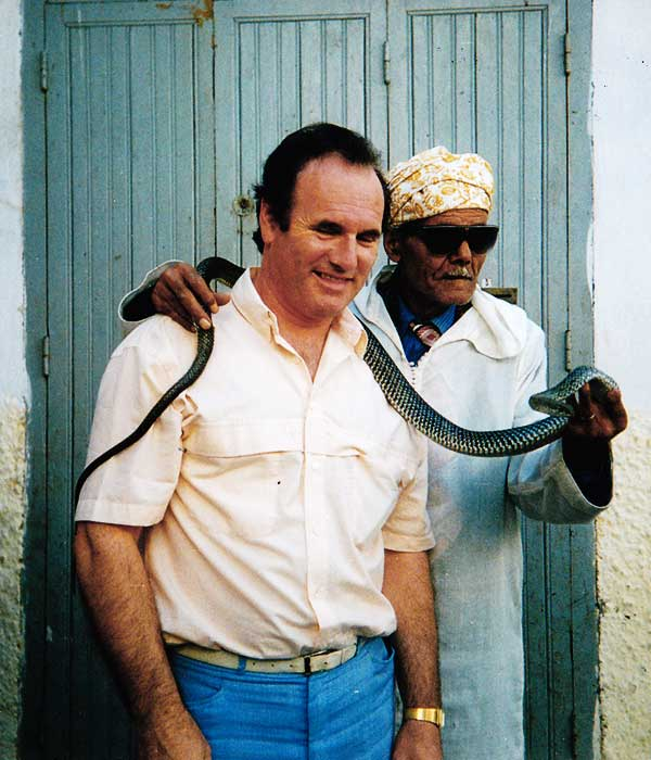 nineteen seventies photo close up of sean in beige shirt and blue trousers in morocco with a snake charmer and his snake wrapped uncomfortably around seans neck